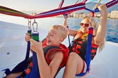 De moeder en de zoon zitten in motorboot en klaar aan paraglide royalty-vrije stock afbeelding