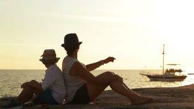 De moeder en de zoon zitten op het strand bij zonsondergang lettend op een schip voorbijgaan stock videobeelden
