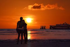 De moeder en de dochter bekijken zonsondergang op het strand royalty-vrije stock foto's