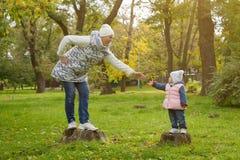 De moeder en de dochter bevinden zich op de stompen in parkland en geven elkaar handen naar in een warme de herfstdag royalty-vrije stock foto