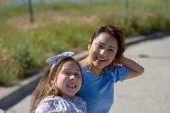 De Moeder en de Dochter die van Latina en op straat in de voorsteden glimlachen lachen stock afbeelding