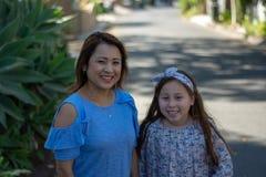 De Moeder en de Dochter die van Latina en op straat in de voorsteden glimlachen lachen royalty-vrije stock afbeeldingen