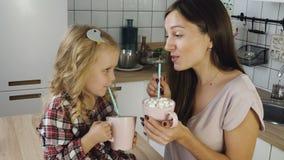 De moeder en de dochter drinken cacao met heemst stock footage