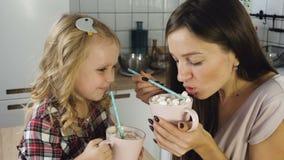 De moeder en de dochter drinken cacao met heemst stock videobeelden