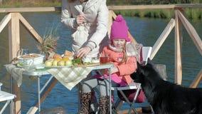 De moeder en de dochter, een jonge vrouw en een klein meisje in warme kleren, openen a kunnen, dichtbij speelt een hond, een pick stock video