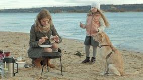 De moeder en de dochter, een meisje met krullend haar, een jonge vrouw in een laag zitten op het strand door de rivier, oceaan, m stock video