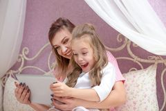De moeder en de dochter gebruiken een tabletcomputer royalty-vrije stock fotografie