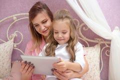 De moeder en de dochter gebruiken een tabletcomputer royalty-vrije stock afbeeldingen