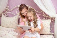 De moeder en de dochter gebruiken een tabletcomputer stock afbeelding