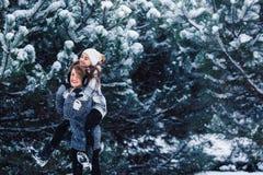 De moeder en de dochter hebben pret het spelen in het de winterbos stock afbeelding