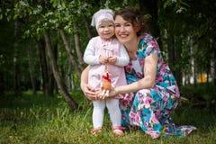 De moeder en de dochter hebben pret in de park en appelboom met witte bloemen Stock Foto