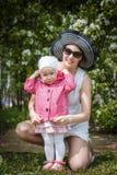 De moeder en de dochter hebben pret in de park en appelboom met witte bloemen Royalty-vrije Stock Foto