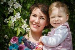 De moeder en de dochter hebben pret in de park en appelboom met witte bloemen Royalty-vrije Stock Afbeelding