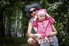 De moeder en de dochter hebben pret in de park en appelboom met witte bloemen Royalty-vrije Stock Fotografie