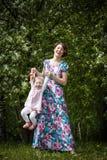 De moeder en de dochter hebben pret in de park en appelboom met witte bloemen Stock Foto's