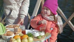 De moeder en de dochter, de jonge vrouw en het meisje in warme kleren, brengen een plaatpannekoeken, picknick door de rivier op a stock video