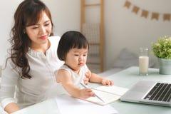 De moeder en de dochter leren te schrijven Stock Foto