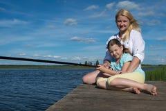 De moeder en de dochter rusten op de pijler van een mooi meer stock foto's
