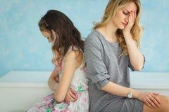 De moeder en de dochter zitten naast rijtjes elkaar, spreken niet Conflict stock afbeeldingen