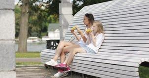 De moeder en de dochter zitten op een bank in het park en eten heet graan stock videobeelden