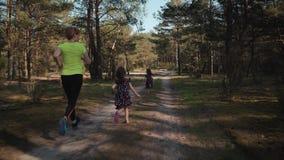 De moeder en de dochters lopen in het de zomerbos stock footage