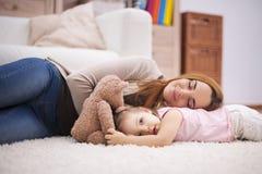 De moeder en haar baby hebben een dutje Stock Foto