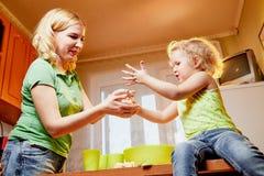 De moeder en haar drie jaar oude blondedochter koken in een keuken Gelukkig mamma en klein meisje met het deeg royalty-vrije stock foto's