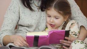 De moeder en haar weinig dochter lezen samen thuis het boek stock video