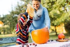 De moeder en het kind bereiden pompoen op Halloween voor Stock Fotografie
