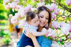 De moeder en het kind hebben een lasure in Magnoliatuin Royalty-vrije Stock Afbeelding
