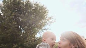De moeder en het kind hebben pret in het park bij zonsondergang De moeder werpt baby, baby het glimlachen stock videobeelden