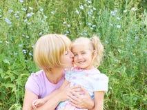 De moeder en het kind koesteren en hebben pret openlucht in aard stock foto
