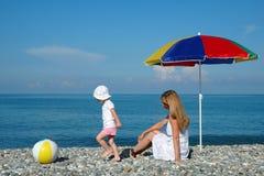 De moeder en het kind spelen een bal bij kust Royalty-vrije Stock Afbeelding