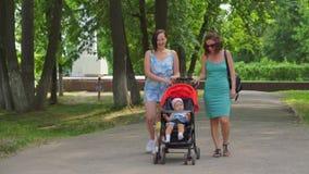 De moeder en het meisje rollen een kind in een wandelwagen stock videobeelden