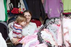 De moeder en 2 jaar dochter kiezen slijtage Royalty-vrije Stock Afbeeldingen
