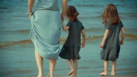 De moeder en twee dochters bevinden zich in het water op een strand stock footage