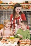 De moeder en twee kinderen bij het maken van Halloween behandelen Stock Afbeelding