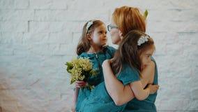 De moeder en twee kleine dochters koesteren elkaar stock footage