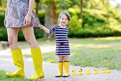 De moeder en weinig aanbiddelijk peuterkind in gele rubberlaarzen, familie kijken, in de zomerpark Mooie vrouw en leuk Stock Foto