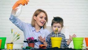 De moeder en de zoon geven geplante bloemen in de zomer water Concept zaailingen stock videobeelden
