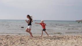 De moeder en de zoon lopen langs het zandige strand De zoonsspelen met mamma halen binnen op het overzees in stock video
