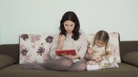 De moeder gebruikt digitale tablet en haar dochter gebruikt smartphonezitting op bank stock footage