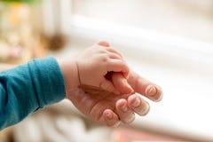 De moeder gebruikt haar hand om de uiterst kleine hand van haar baby te houden om hem te maken die haar liefde voelen te verwarme stock afbeeldingen