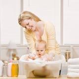 De moeder geeft babymeisje een bad Stock Foto's