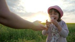 De moeder geeft de drank van de kinddochter schoon zuiver water op zonsondergangaard, leuk vrouwelijk meisjes drinkwater van glas stock video