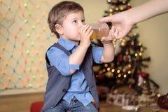De moeder geeft een fles aan haar zoon op een Kerstmisvooravond Royalty-vrije Stock Foto's