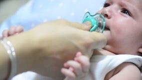 De moeder geeft de fopspeen aan baby en de baby neemt de fopspeen en wordt stil stock video