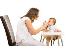 De moeder geeft haar baby om yoghurt te eten Stock Foto's
