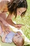 De moeder geeft zonbescherming aan baby Stock Afbeelding