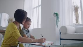 De moeder in geel jasje en de zoon in t-shirt zitten bij de lijst en trekken zich kleurenpotloden op papier samen Gelukkige kinde stock footage